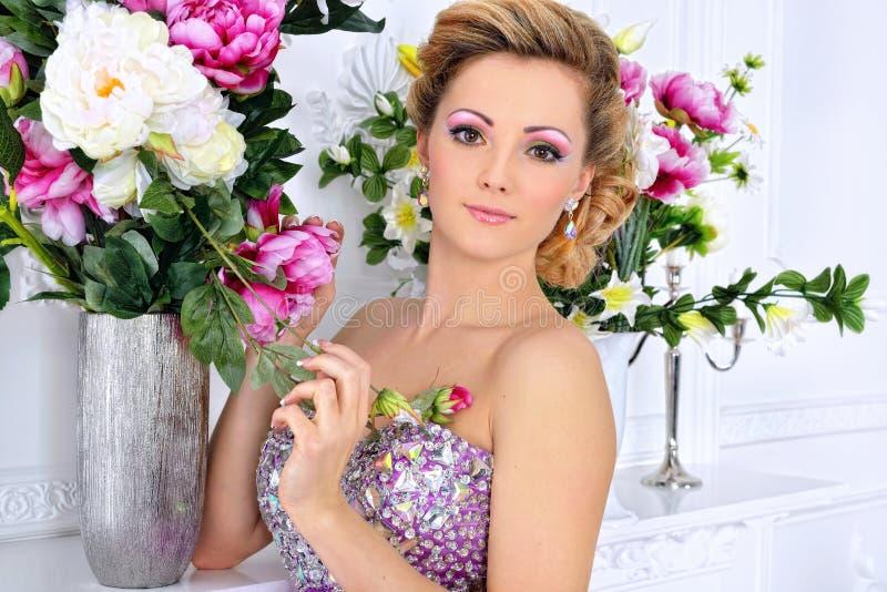 Beautiful woman in violet dress in luxury studio. stock photos