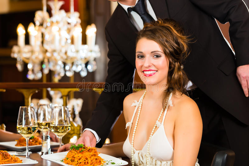 Beautiful woman and waiter in fine dining restaurant. Pretty women sitting at a table in a fine dining restaurant, waiter served the dinner - a large chandelier royalty free stock image