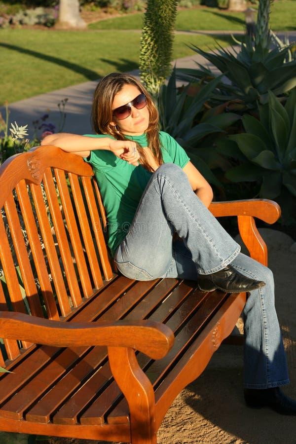 Beautiful woman waiting at the park (vertical) royalty free stock photos