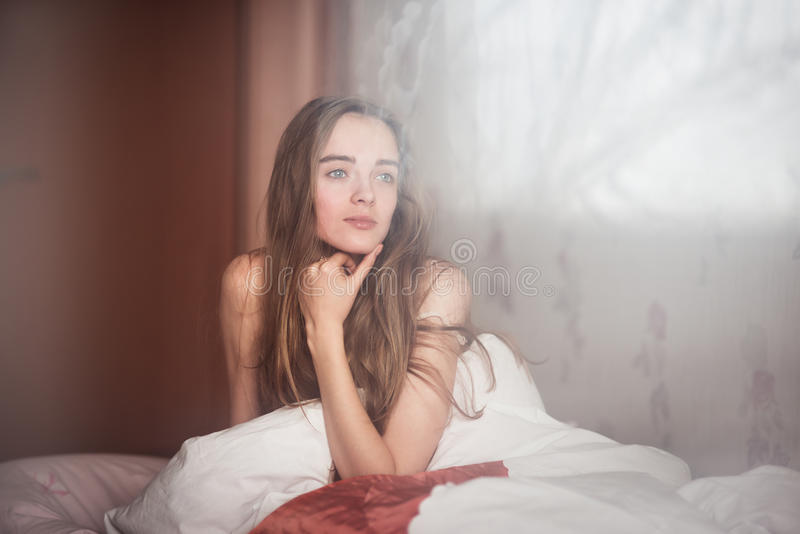 Beautiful woman waking up in the bedroom after good night sleep. Young beautiful woman waking up in the bedroom after good night sleep stock photography
