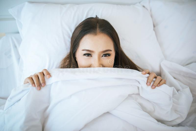 Beautiful woman waking up in her bed royalty free stock photo
