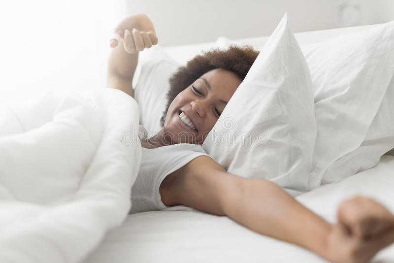 Beautiful woman waking up. In her bed, she is smiling and stretching royalty free stock images