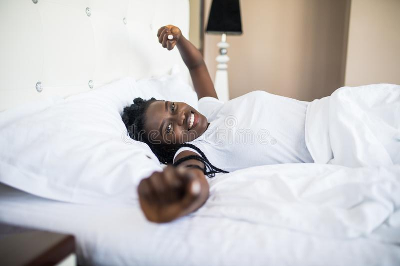 Beautiful afro american woman waking up in her bed, she is smiling and stretching. Beautiful woman waking up in her bed, she is smiling and stretching stock photography