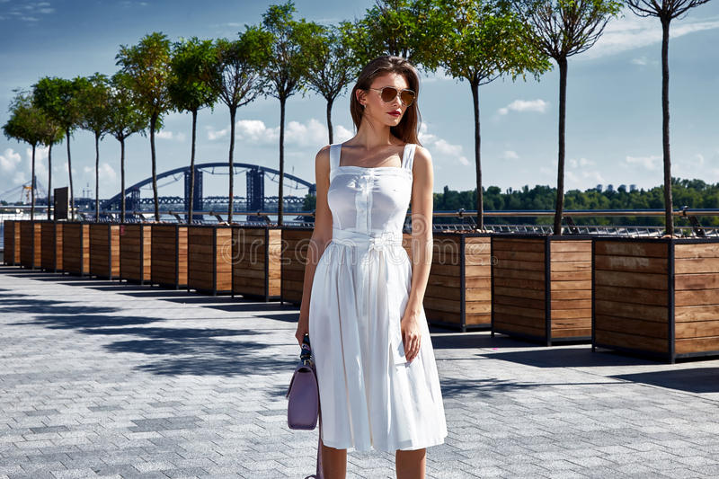 Beautiful woman walk on the street square wear fashion style clothes white cotton dress accessory bag jewelry sunglasses alley av. Enue romantic date summer sun royalty free stock photo