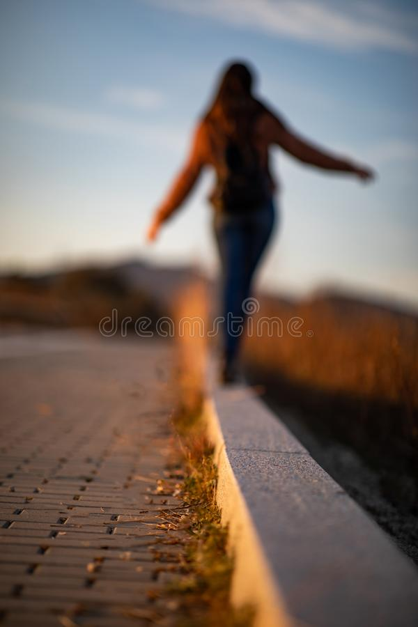 Beautiful woman walking and balancing on street curb or curbstone during sunset stock image