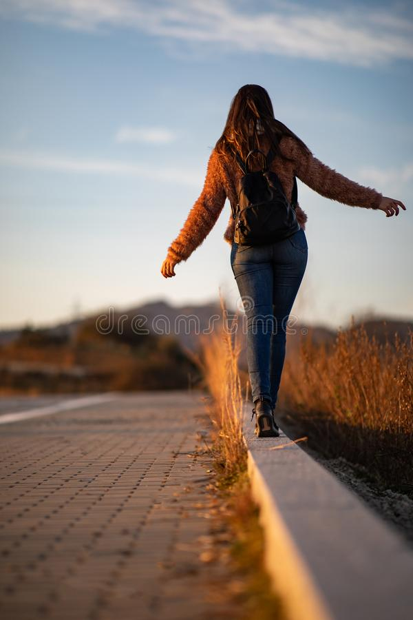 Beautiful woman walking and balancing on street curb or curbstone during sunset royalty free stock photo