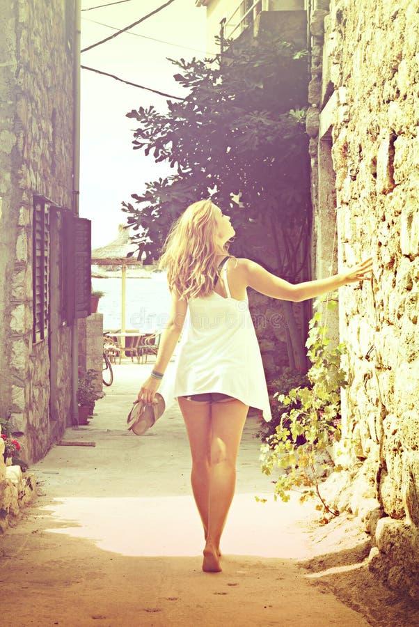 Beautiful woman walking barefoot in the street, cross process stock image