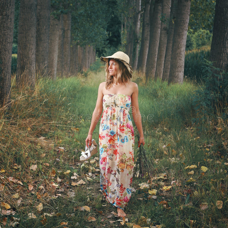 Beautiful woman walking barefooted in nature. Beautiful woman walking barefooted in a meadow with trees royalty free stock photo