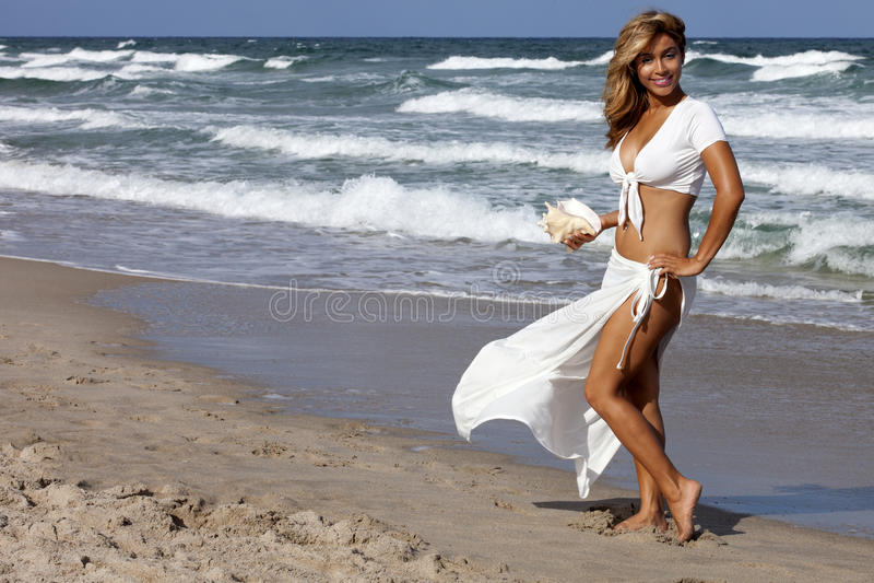 Beautiful woman walking on beach stock images