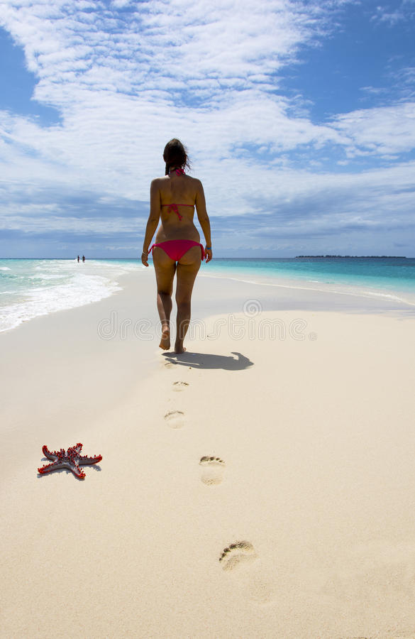 Beautiful woman walking on the beach royalty free stock images