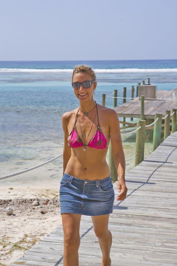 Beautiful Woman walking on a Cayman Island Dock. Beautiful smiling Woman walking on a Cayman Island Dock royalty free stock image