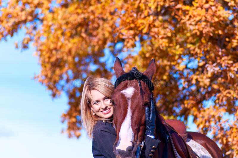 Beautiful woman walking with horse. And oak tree as background stock photography