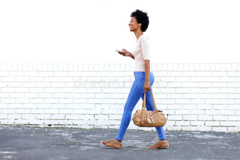 Beautiful woman walking and listening to music with purse stock images