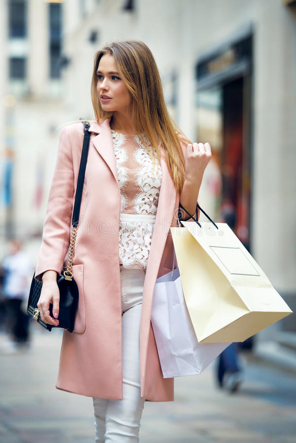 Beautiful woman walking on New York street with bags after she shopping royalty free stock image