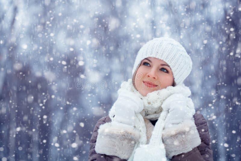 Beautiful woman walking outdoors under snowfall stock photography