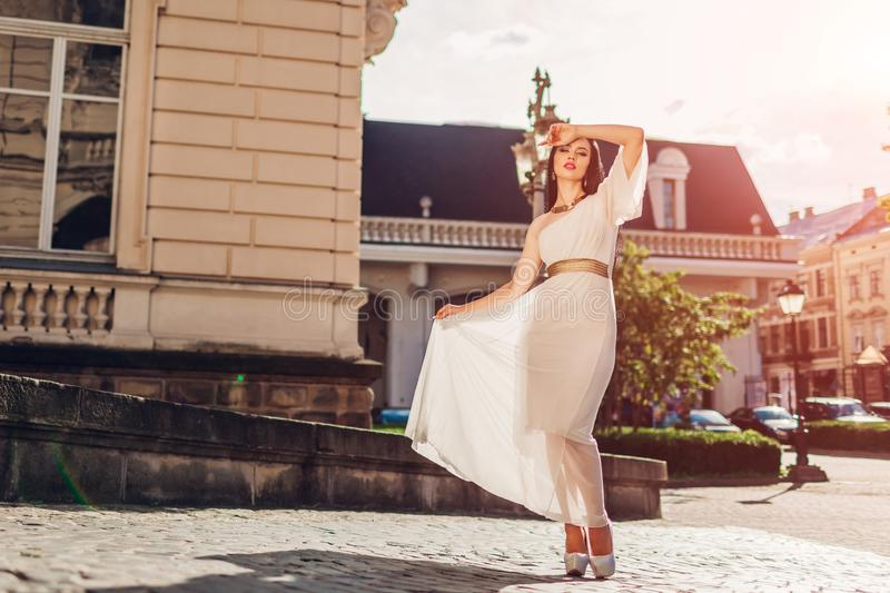 Beautiful woman walking in white wedding dress outdoors. One shoulder dress with accessories and jewellery stock image