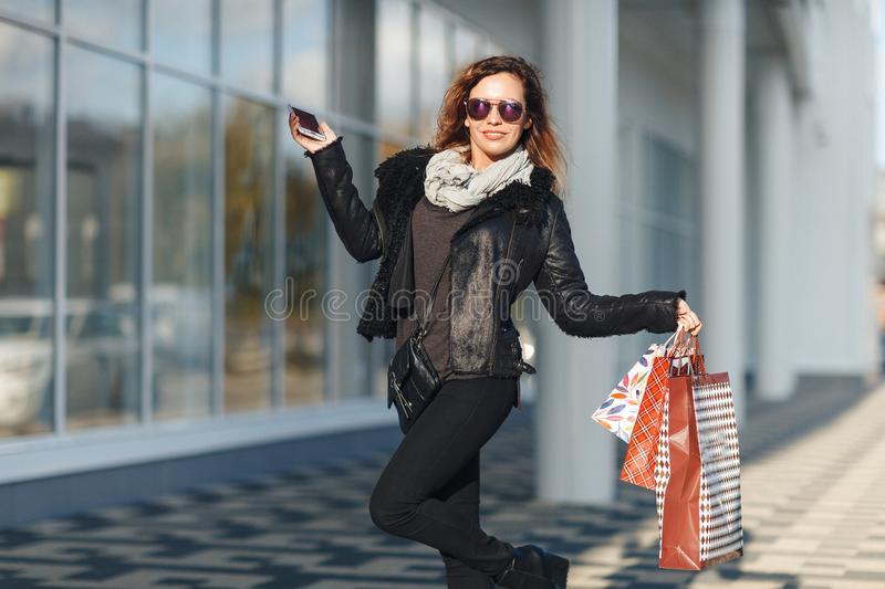 A beautiful woman walks through the city on shopping, she is very happy of purchases in the period sales. Concept: fashion, shoppi royalty free stock images