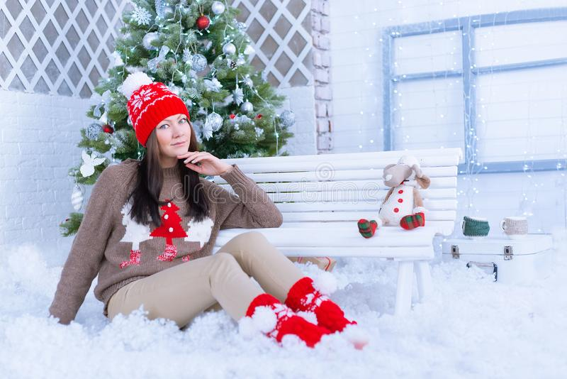 Beautiful woman in warm clothing against the background of the Christmas tree. Very beautiful girl with blue eyes in a red hat and stock images