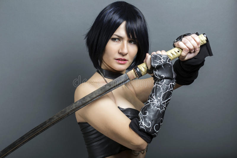 Beautiful woman-warrior with sword. On grey background royalty free stock photography