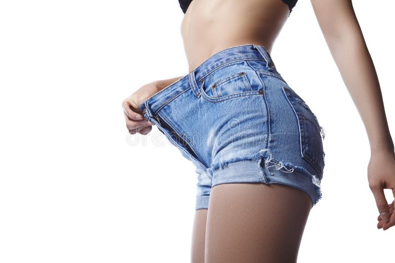 Beautiful woman is wearing big blue jeans shorts and showing her weight loss. Perfect body shapes, sports hips royalty free stock photo