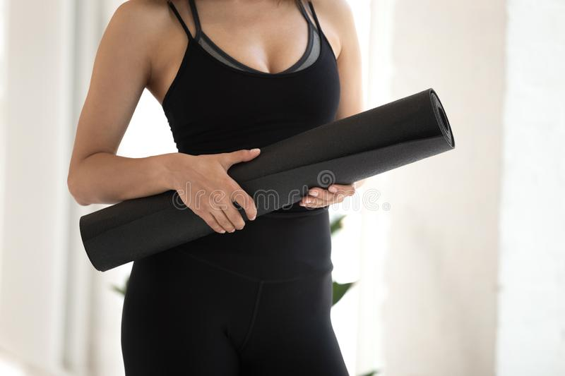 Beautiful woman wearing black sportswear holding yoga mat close up royalty free stock photos