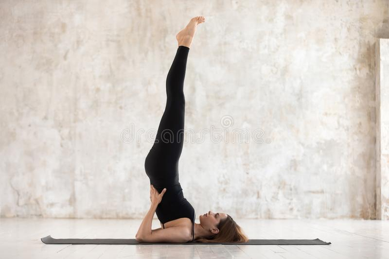 Beautiful woman practicing yoga, Salamba Sarvangasana pose, Shoulder stand royalty free stock images