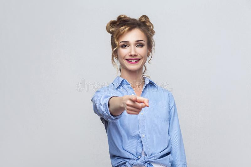 The beautiful woman, wearing blue shirt, having happiness looks, pointing finger at camera. royalty free stock images