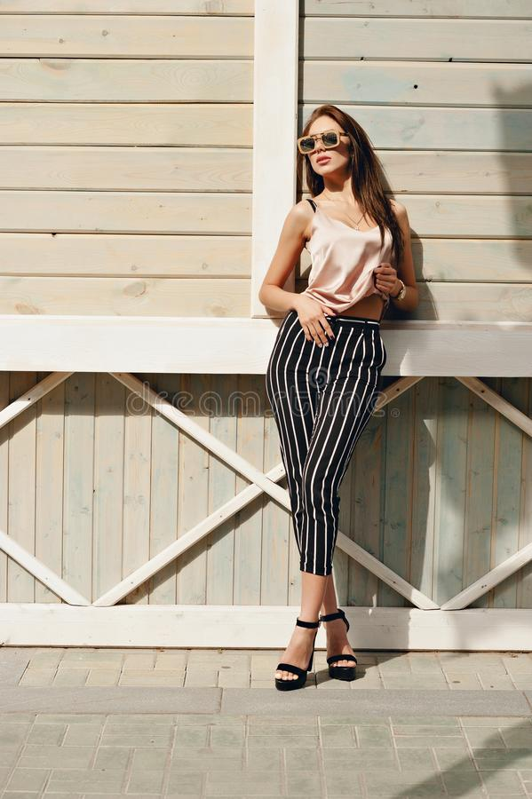 Beautiful woman, wearing dark glasses, against the background of a tree wall. The model wears stylish clothes, beige royalty free stock image