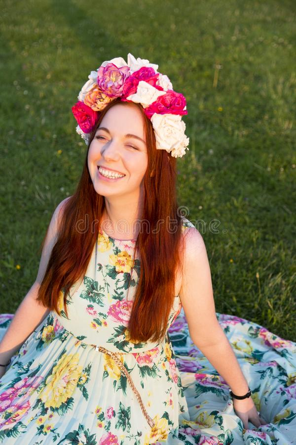 Beautiful woman wearing floral wreath and smiling. Beautiful woman wearing floral wreath on her hed, sitting on grass outdoors and smiling royalty free stock image