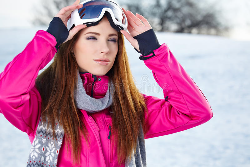 Beautiful woman wearing goggles in snowy winter stock image