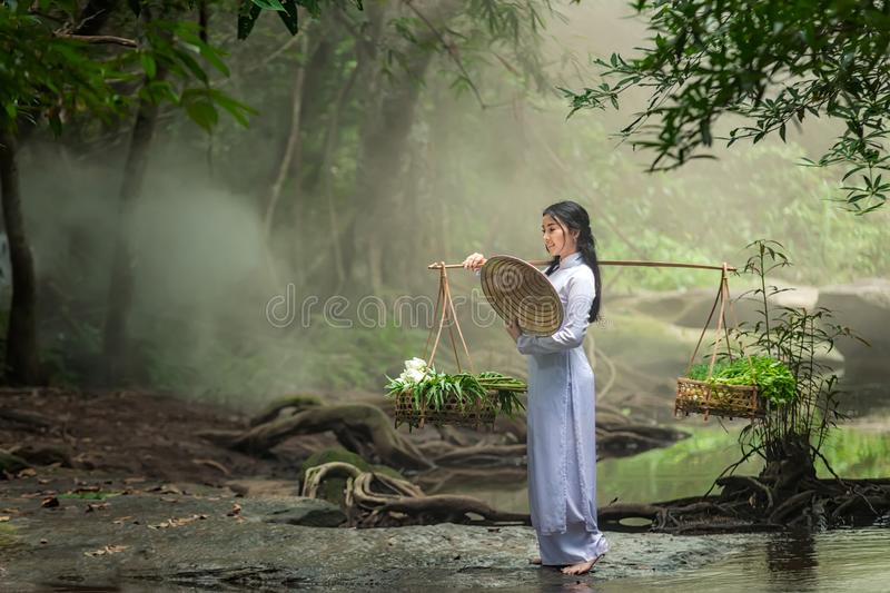 Beautiful woman wearing a hat Dress Ao Dai traditional Vietnamese dress standing in the forest. royalty free stock photo