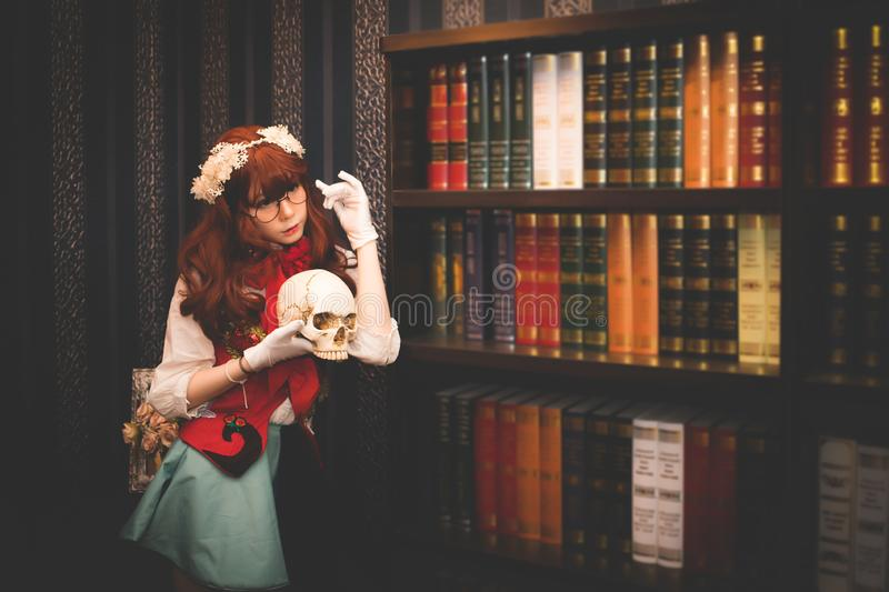 A beautiful woman wearing a Japanese style cosplay costume and wearing glasses is standing, holding the skull in the library. stock photography
