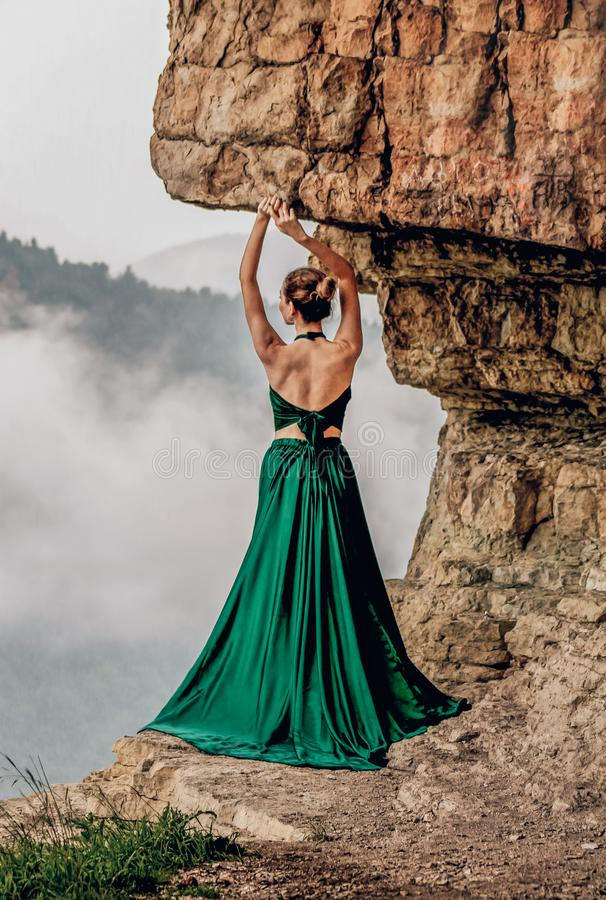 Beautiful woman wearing long green dress standing on the edge of a cliff. Mezmay. Russian mountains. stock images