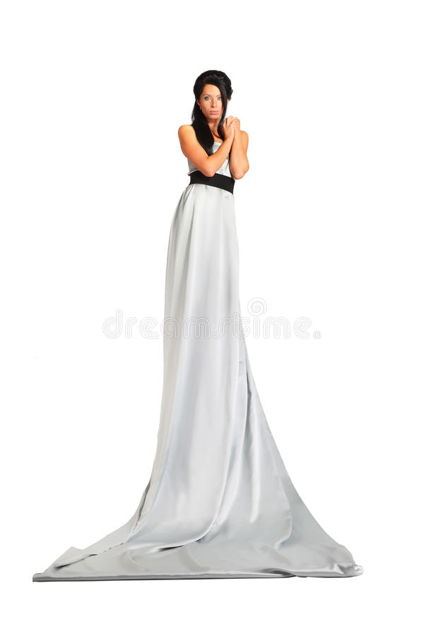 Beautiful woman wearing long silver dress stands royalty free stock photo