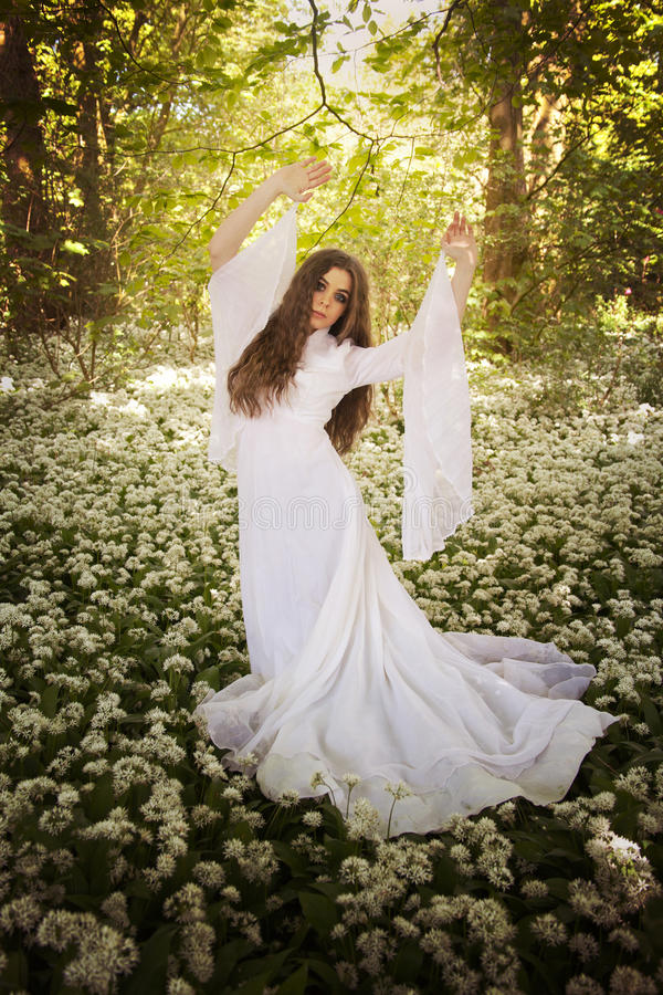 Beautiful woman wearing a long white dress dancing in a forest stock images