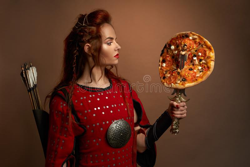 Medieval female warrior and pizza. Beautiful woman wearing in medieval red tunic holding dagger with delicious pizza. Gorgeous, brave warrior with arrows behind royalty free stock photos
