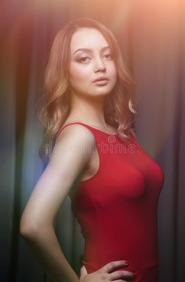 Charming Brunette In A Red Dress Posing On A Black