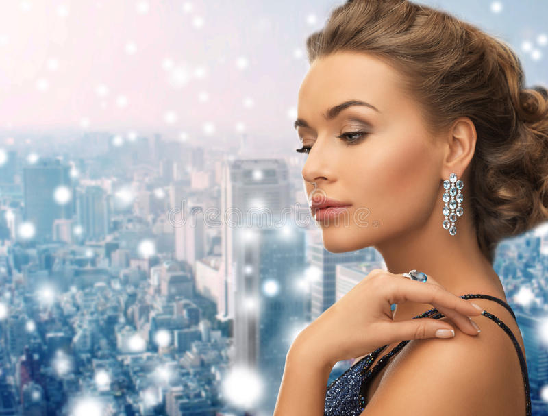 Beautiful woman wearing ring and earrings. People, holidays, christmas and glamour concept - beautiful woman in evening dress wearing ring and earrings over royalty free stock image