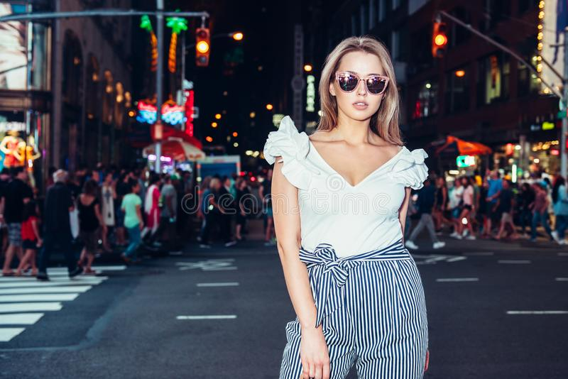 Beautiful woman wearing stylish fashionable outfit posing on night city street in New York.  royalty free stock photos