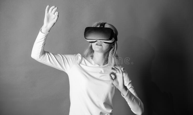 Beautiful woman wearing virtual reality goggles in studio. Woman using virtual reality headset. Happy woman exploring royalty free stock image