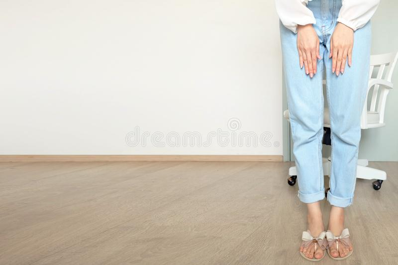Beautiful Woman Wearing White Shirt and Blue Jeans Isolated. Portrait of Female Standing with White Chair Isolated at White stock photography
