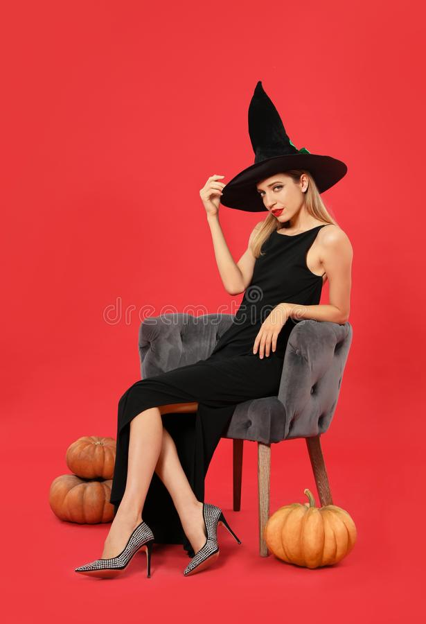 Beautiful woman wearing witch costume in armchair and pumpkins on red background stock photo