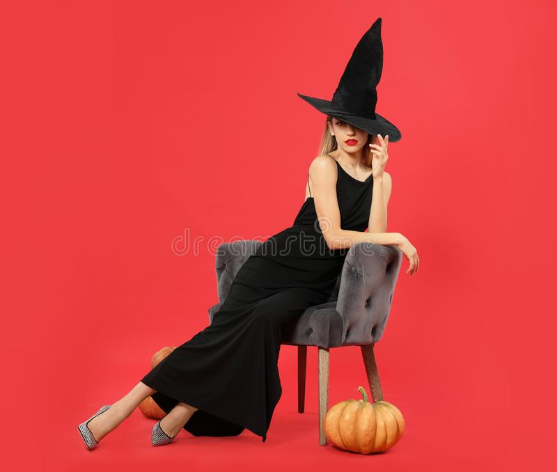 Beautiful woman wearing witch costume in armchair and pumpkins on red background. Halloween party stock photos