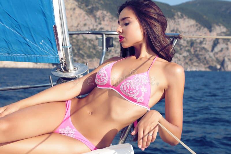 Beautiful woman wears pink bikini, relaxing on yacht in the sea royalty free stock images