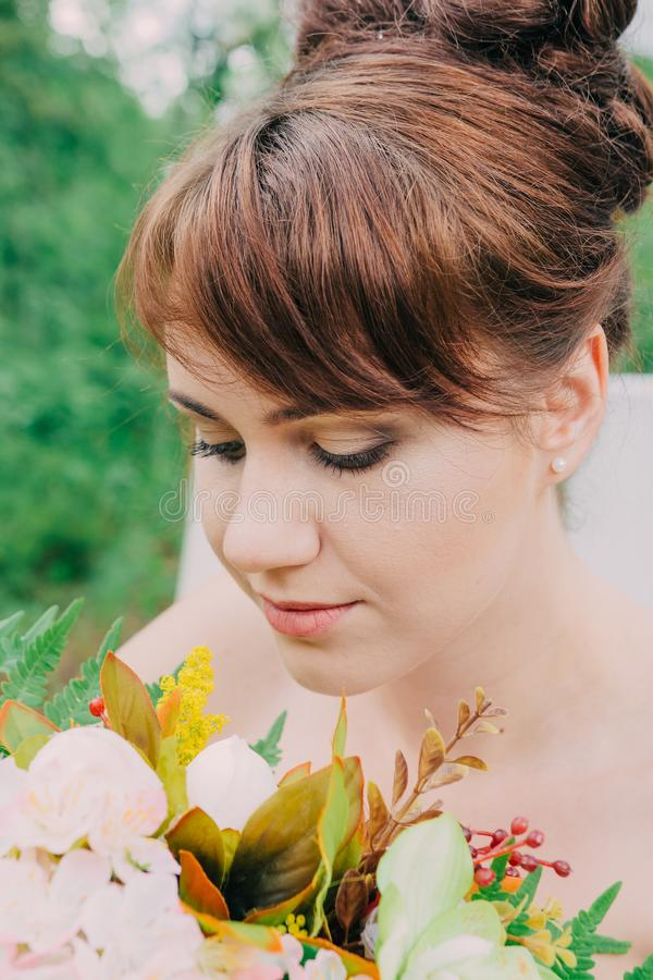 Beautiful woman in a wedding dress on a photozone decorated with fresh flowers, posing and portrait. stock photography
