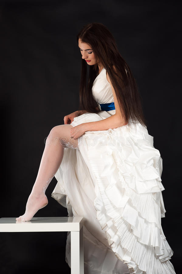 Beautiful woman in a wedding dress straightens stockings. Isolated on black background royalty free stock photo