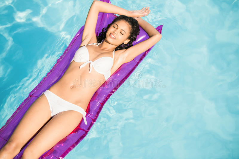 Beautiful woman in white bikini relaxing on air bed in pool stock images