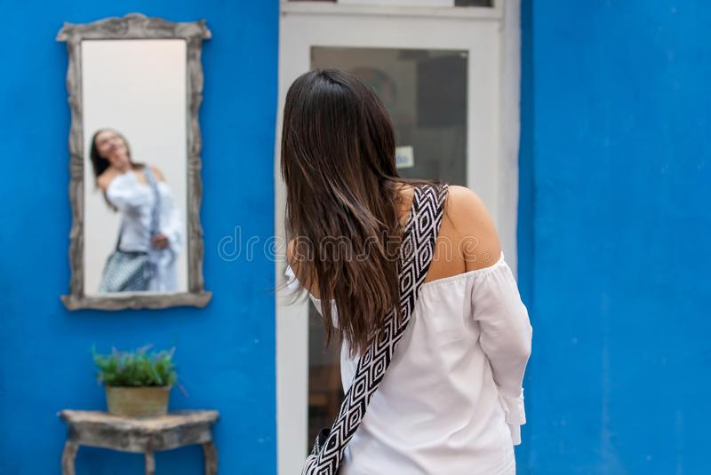 Beautiful woman on white dress looking at herself on a mirror on the colorful streets of the colonial walled city of Cartagena de. A Beautiful woman on white stock photo