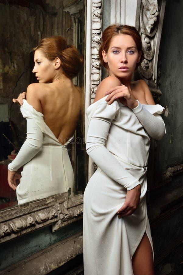 Woman in White Sleeveless Dress Sitting on Gray Concrete