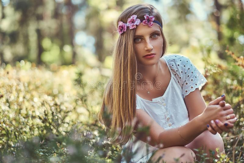 Beautiful woman in a white dress and purple wreath on head posing in a green autumn forest. royalty free stock photo